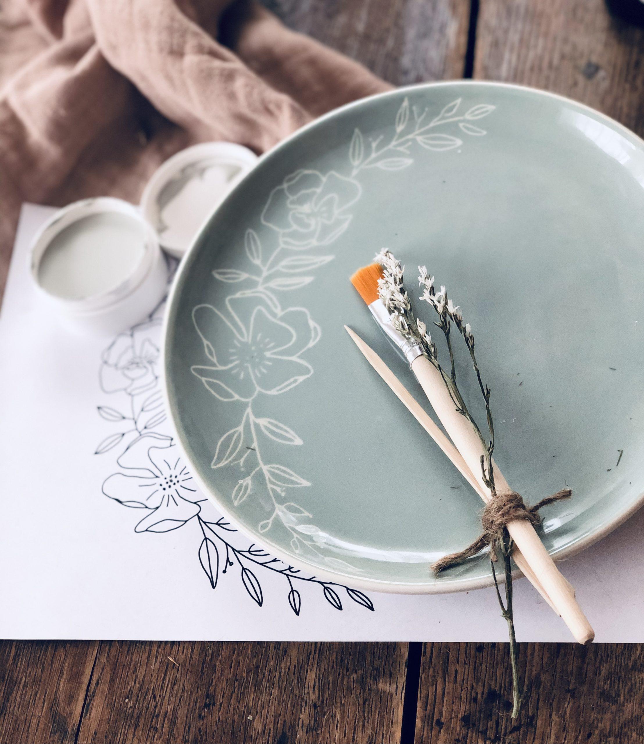 Teller in Salbei mit eingekratzter Blumenranke. Auf dem Teller liegt ein Pinsel