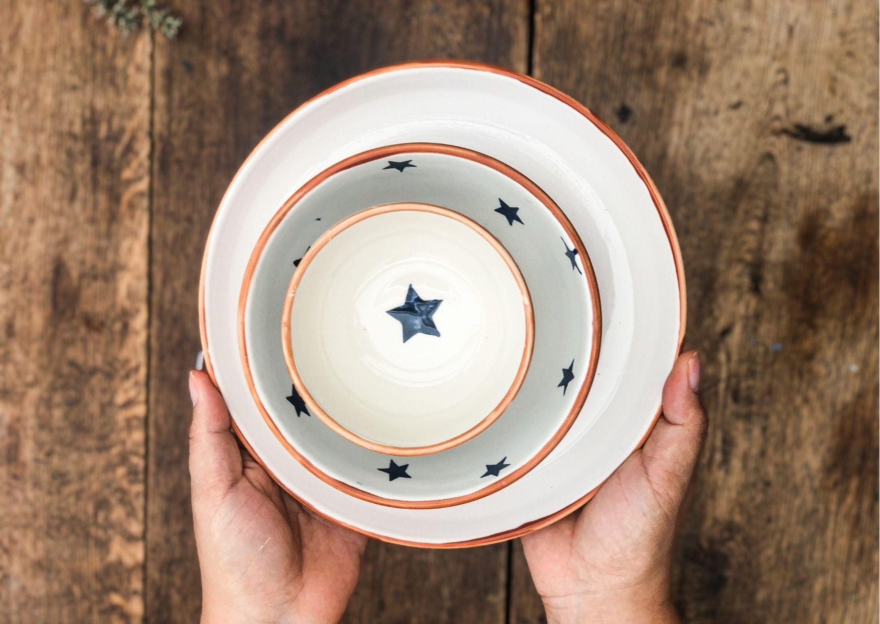 Handbemaltes Keramikgeschirr mit Sterndesign in Händen gehalten